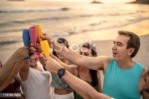 istock Group of friends at celebratory toast celebrating new year at beach 1197847600