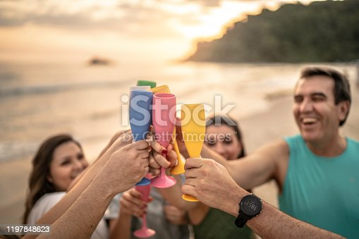 istock Group of friends at celebratory toast celebrating new year at beach 1197848623