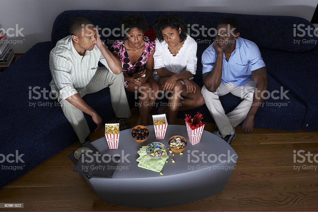 Gruppo di amici a casa guardare la televisione foto stock royalty-free