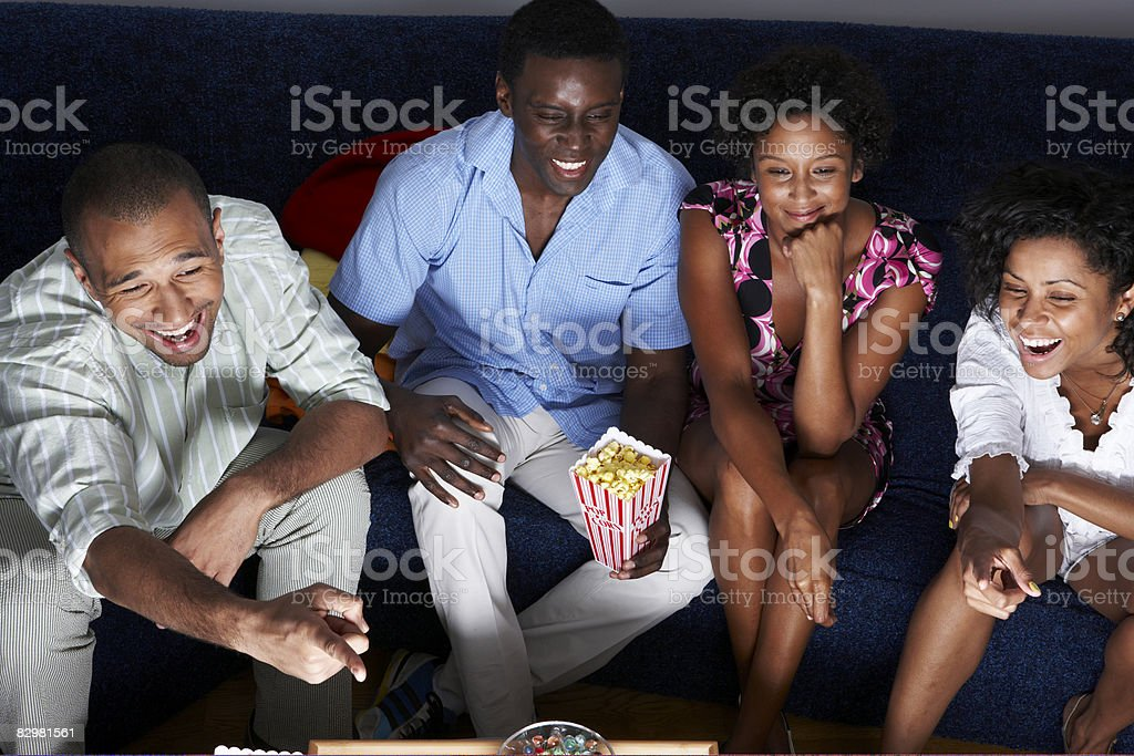 Group of friends at home watching television royalty free stockfoto