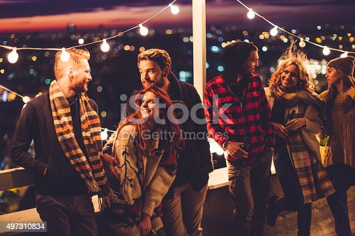 Couple of friends having a party on the rooftop of the building at sunset. Drinking bottles of beer and taking. Wearing knitted sweaters, hats and scarfs. They are happy and joyful.