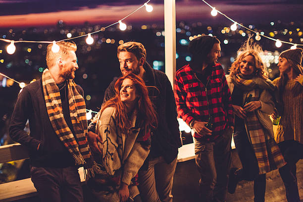 group of friends at rooftop party - party social event stock pictures, royalty-free photos & images