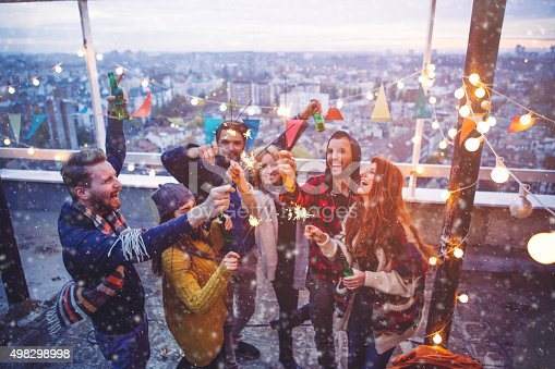 Couple of friends having a party on the rooftop of the building while snowing. Drinking bottles of beer and holding sparklers.. Wearing knitted sweaters, hats and scarfs. They are happy and joyful.