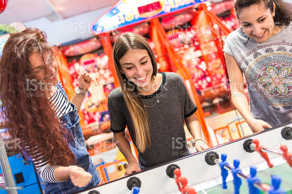Group of friends at the amusement arcade playing foosball stock photo