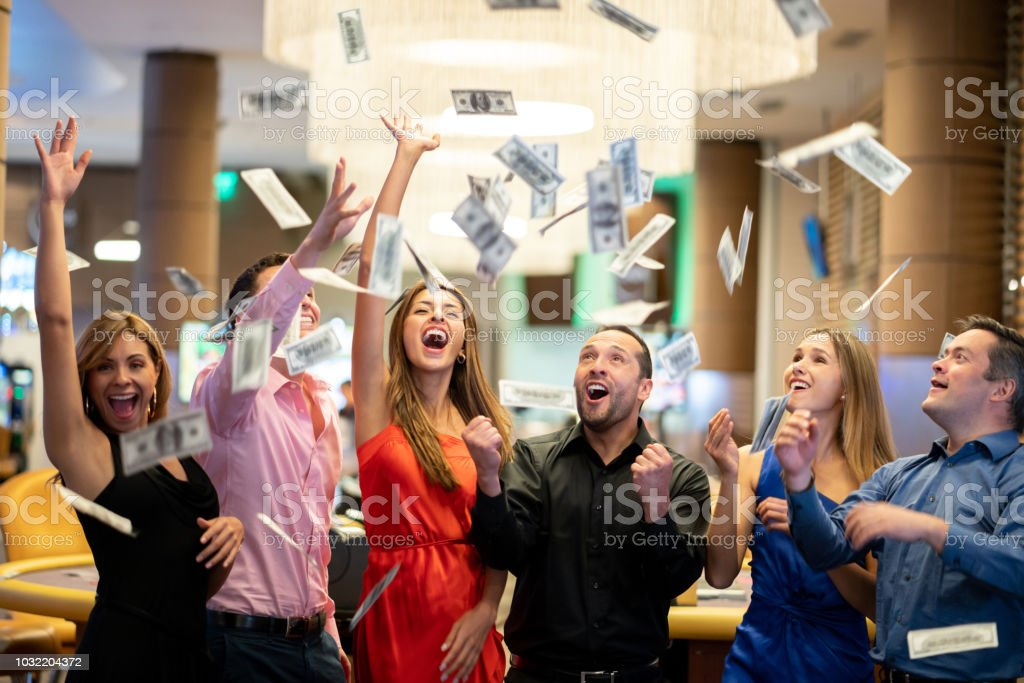 Group of friends at the casino celebrating a big win throwing money to the air stock photo