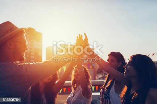 istock Group of friends at the rooftop doing high five 625506764