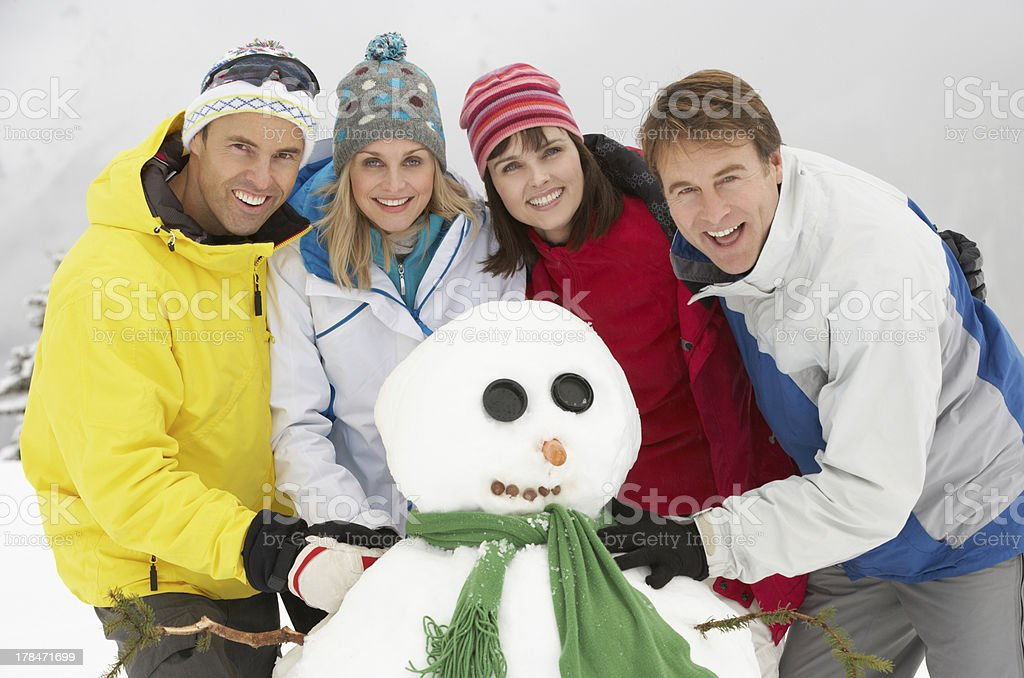 Group Of Friends Building Snowman On Ski Holiday In Mountains stock photo