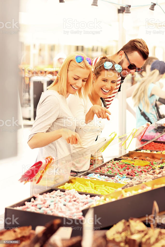 Group of friends buying jelly sweets on market stock photo