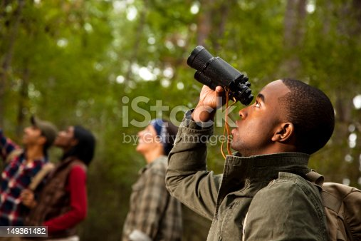 Group of friends camping and hiking using binoculars
