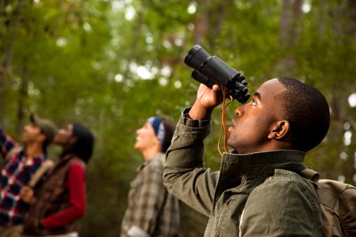 Group of friends camping and hiking using binoculars. Bird watching.