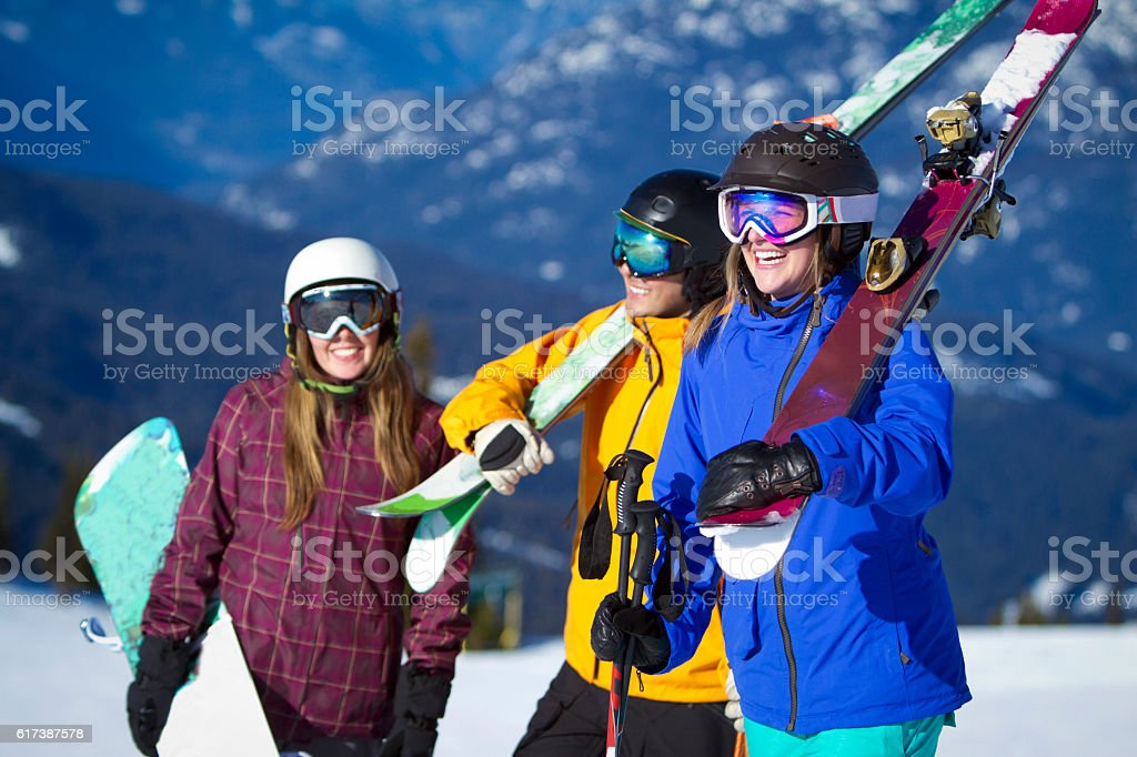 Group of friends carrying ski and snowboard gear. stock photo
