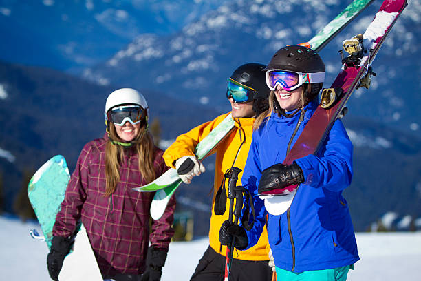 Group of friends carrying ski and snowboard gear. Group of skiers and snowboarding carrying their equipment in mountains and laughing. ski resort stock pictures, royalty-free photos & images
