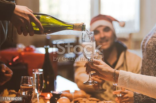 1064325668istockphoto Group of friends celebrating Christmas, preparing flutes with champaign, pouring sparkling wine 1179164225