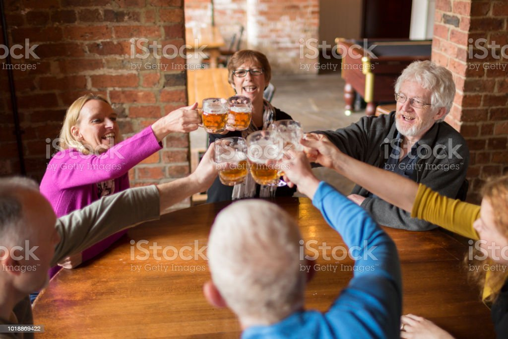 A group of friends celebrating in a bar stock photo