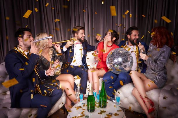 gruppe von freunden feiern neujahr unter fallenden konfetti - club sofa stock-fotos und bilder