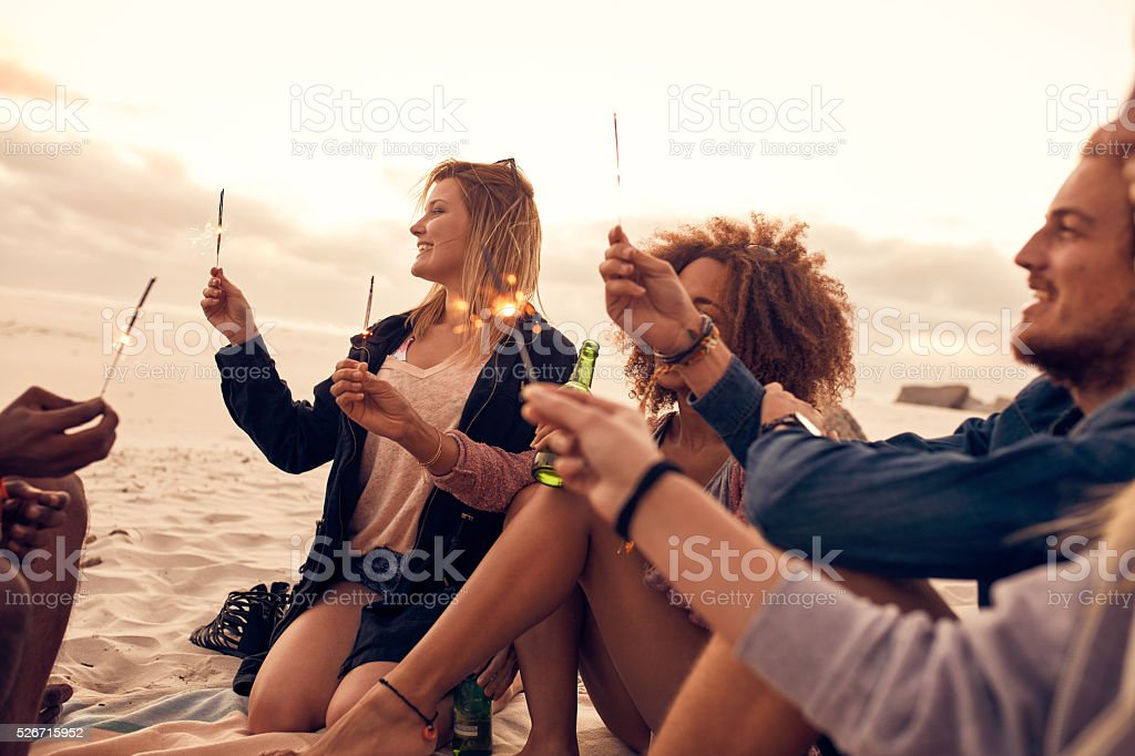 Group of friends celebrating new year's day at the beach stock photo