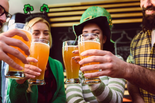 group of friends celebrating st patrick's day at beer pub - st patricks day stock photos and pictures