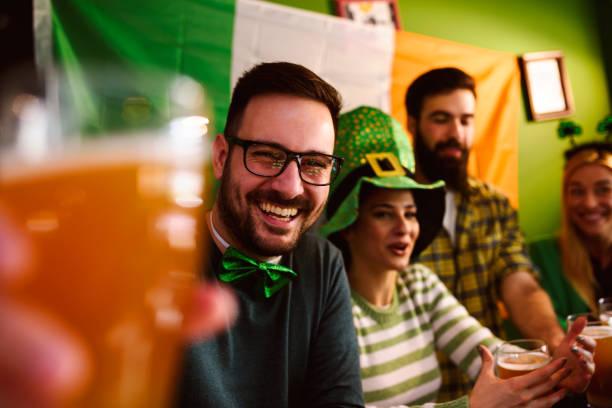 groupe d'amis, célébrer la saint-patrick au pub de la bière - saint patrick photos et images de collection