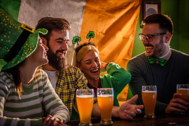 group of friends celebrating st patrick's day at beer pub - st patricks days stock photos and pictures