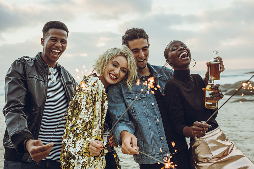 Group of multi-ethnic friends enjoying at beach with sparklers. Young men and women having fun with fireworks at the sea shore.