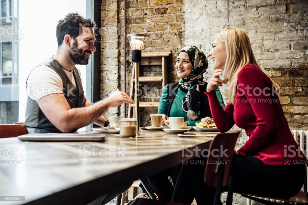 Group of friends chatting in coffee shop stock photo
