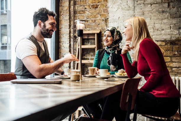 Group of friends chatting in coffee shop Three people sitting at table having conversation, mid adult man with facial hair explaining, two women listening modest clothing stock pictures, royalty-free photos & images