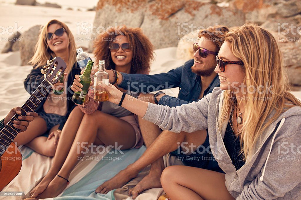 Group of friends cheers with beers at the beach stock photo
