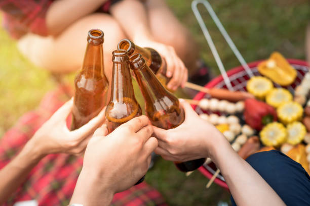 Group of friends clinking bottle of beer during camping outdoor party with barbecue in background stock photo