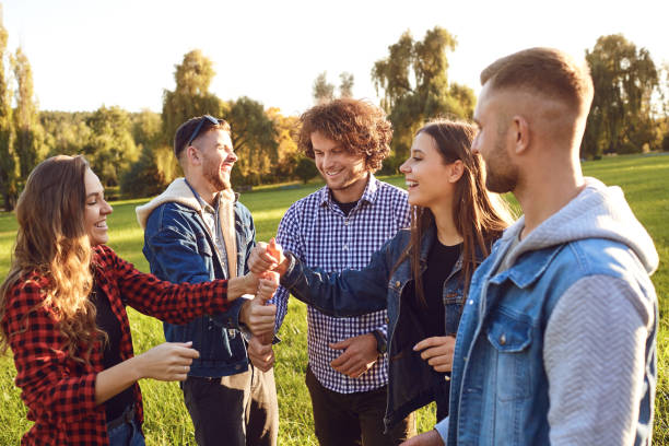 Group of friends connected thumb up in the park. stock photo