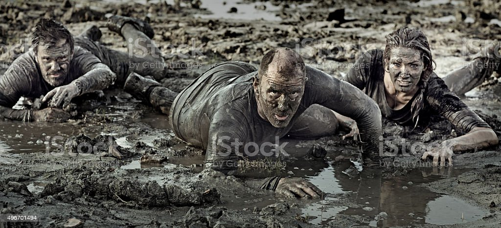 group of friends crawling in mud stock photo