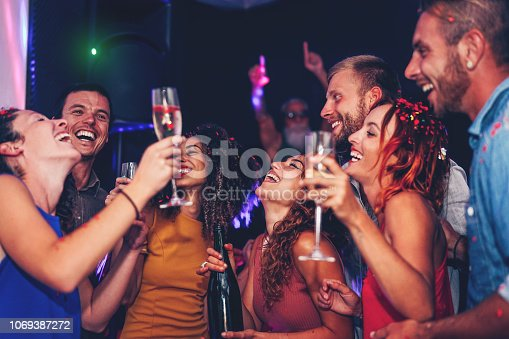 istock Group of friends dancing and drinking champagne at nightclub party - Happy young people having fun celebrating together in disco club - Entertainment, nightlife and youth lifestyle 1069387272