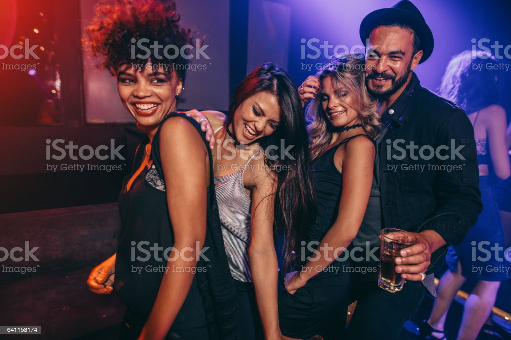 Group of friends dancing at disco club stock photo