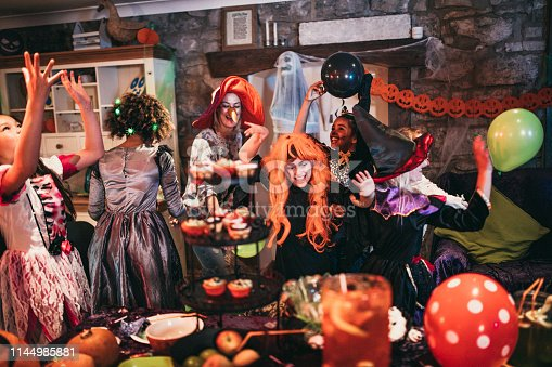 Group of young friends dressed in costumes dancing and playing together at a Halloween party. One of their parents is playing alongside them, also dressed in a costume.