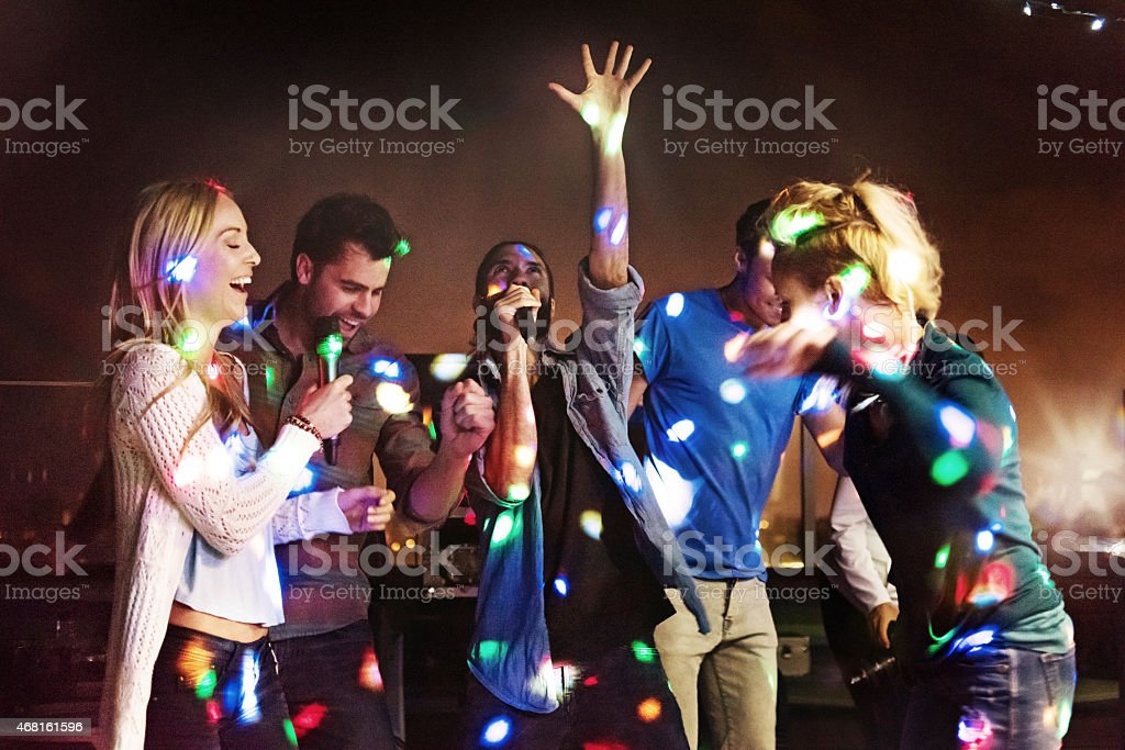 Group of friends doing karaoke stock photo