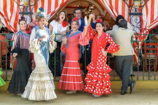 gruppe von freunden in traditionellen kostümen gekleidet und genießen auf der sevillas april fair. - festzugskleidung stock-fotos und bilder