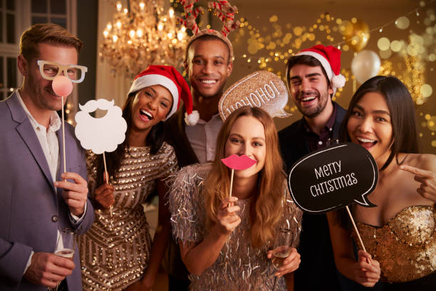 Group Of Friends Dressing Up For Christmas Party Together stock photo