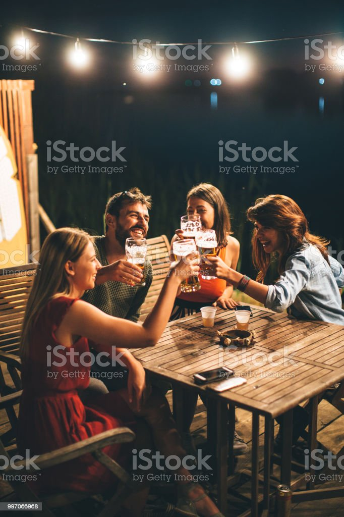 Group of friends drink beer on the terrace and toast during summer night stock photo