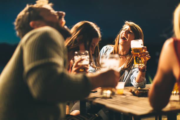 Gruppe von Freunden trinkt Bier auf der Terrasse in der Sommernacht – Foto