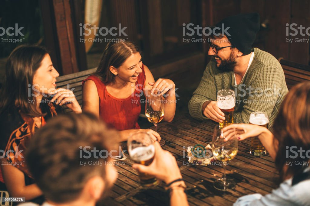 Group of friends drink beer on the terrace during summer night stock photo
