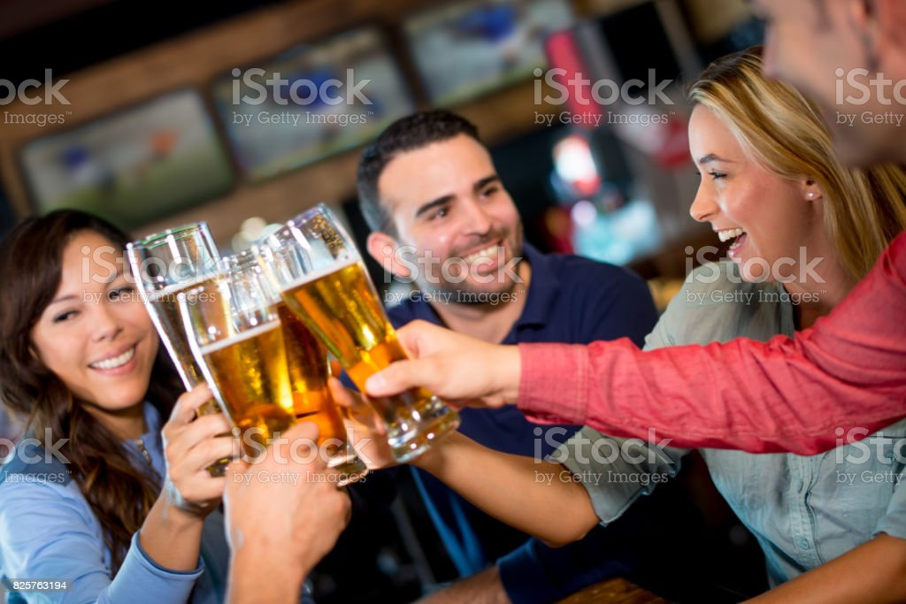 Group of friends drinking at a sports bar and making a toast - foto stock