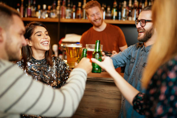 Group of friends drinking beer, chatting and having fun at pub. stock photo