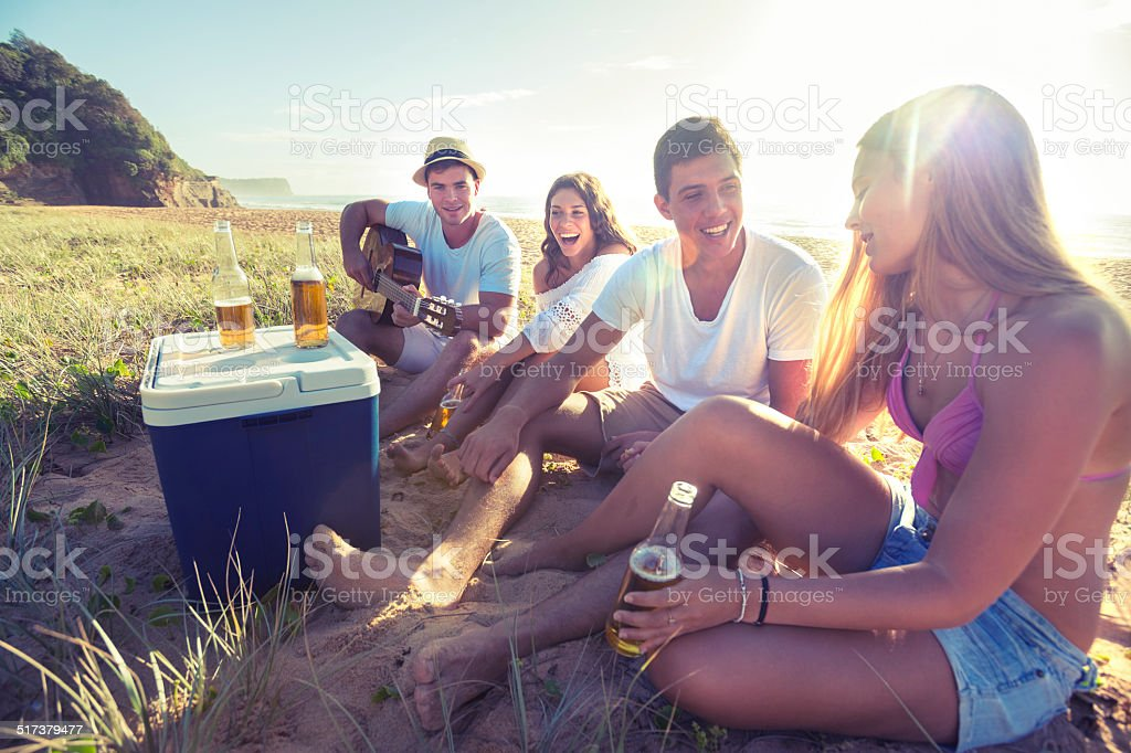 Group of friends drinking beer on the beach stock photo