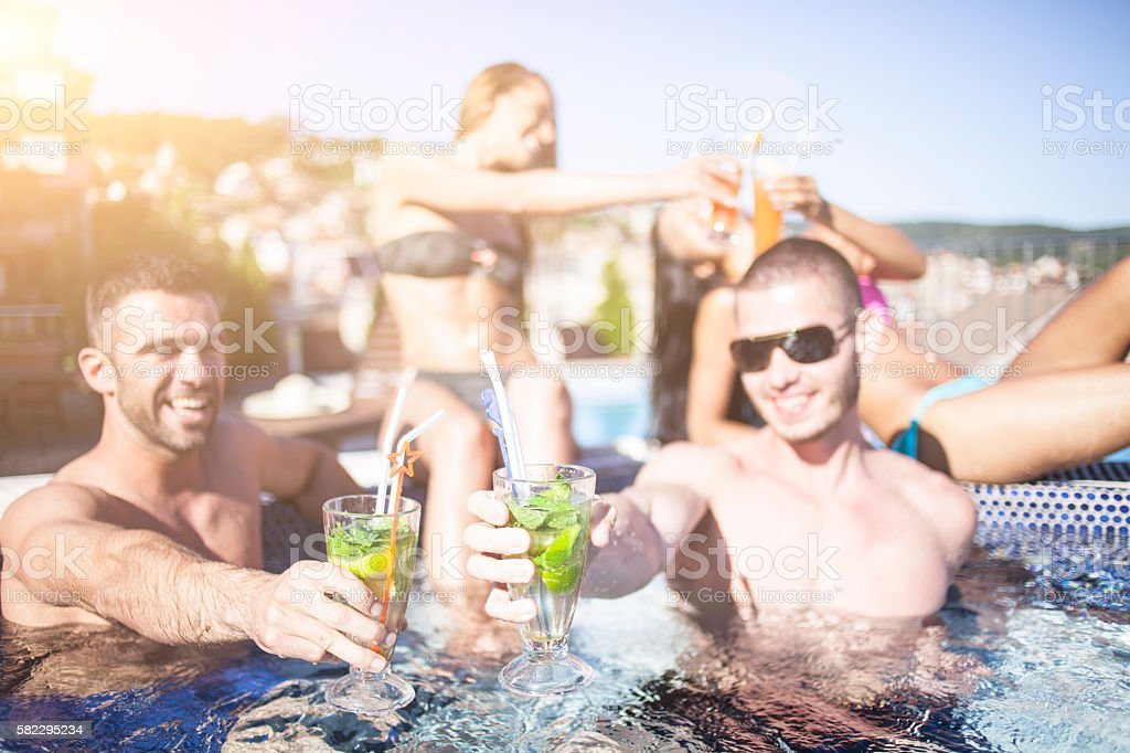 Group of friends drinking cocktails in the pool stock photo