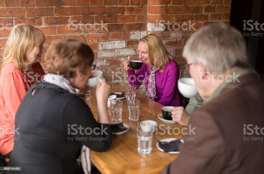 A group of friends drinking coffee in a bar stock photo
