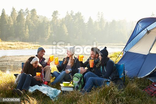 Group of friends drinking outside their tent near a lake