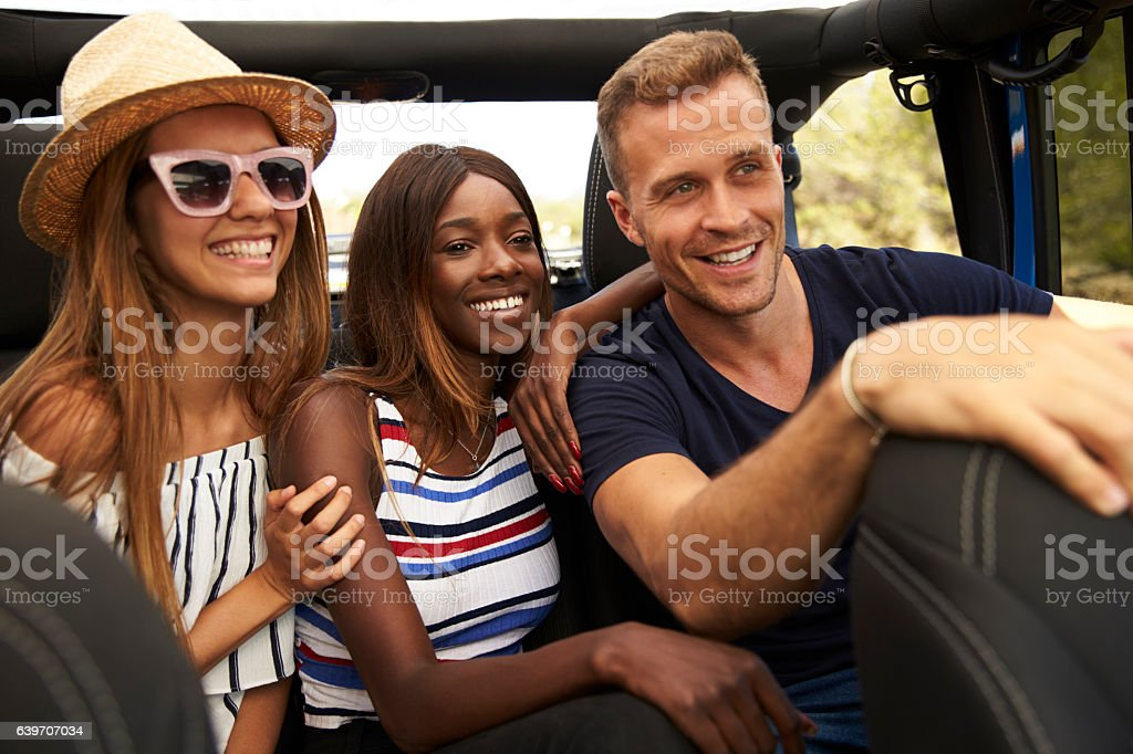 Group Of Friends Driving Open Top Car On Country Road stock photo