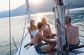 Group of friends during golden hour on the sailboat