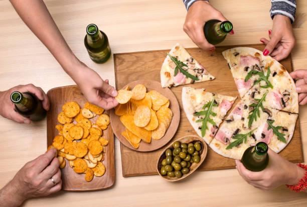 Gruppe von Freunden Essen und Bier zusammen trinken. Fast-Food, Freundschaft, Lifestyle-Konzept. – Foto