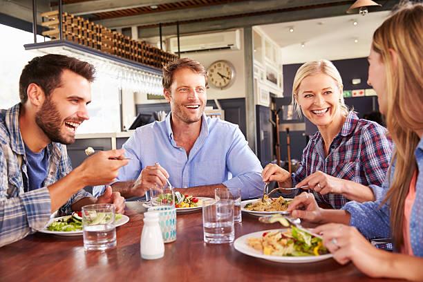 group of friends eating at a restaurant - lunchrast bildbanksfoton och bilder