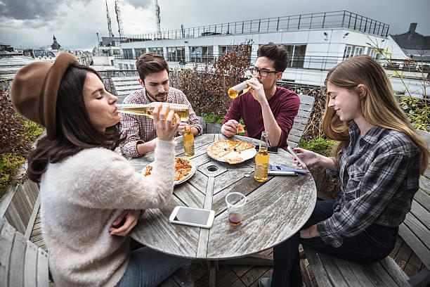 eine gruppe von freunden essen in der küche, die zubereitung von speisen - paletten terrasse stock-fotos und bilder